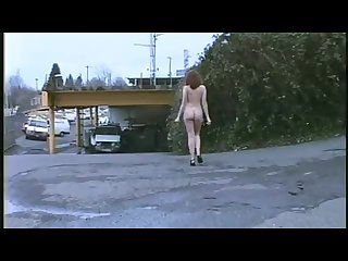 Tall nude girl walks in urban area