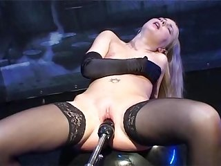 Long gloved blone in stockings fucks dildo machine