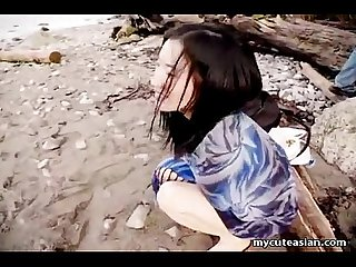 Asian slut is on the beach naked posing