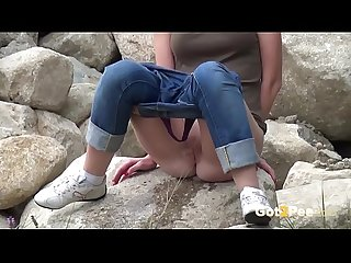 Redhead Pissing - A sexy European babe pees over rocks while outside