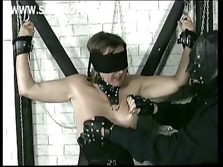 Older slave got blindfolded and chained to a wall and hit on her tits by master