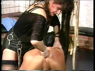 Mistress wearing leather puts some lube on slave with his ass and fist fucks him