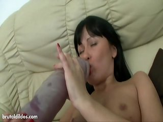 Cute brunette fills her tight pussy with A giant dildo