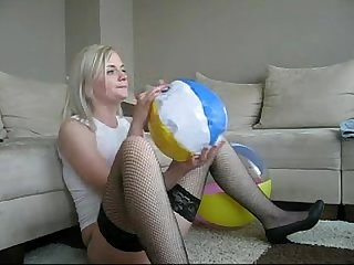 Sophie in miniskirt stockings and red bra playing with beachball