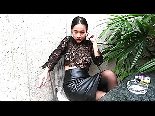 Young girl smokes topless and in leather skirt