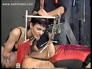 Ebony slave tied to a workbench covered in candlewax got large injection needles in her tits